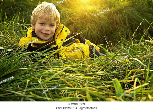 Young boy, lying in the long grass of a ditch in a field, smiling