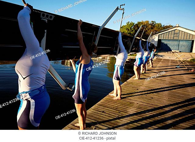 Female rowers lifting scull on sunny lakeside dock