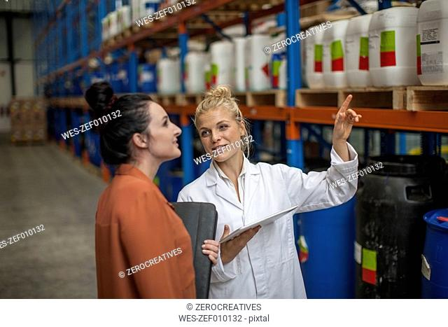 Woman with digital tablet in warehouse talking to woman