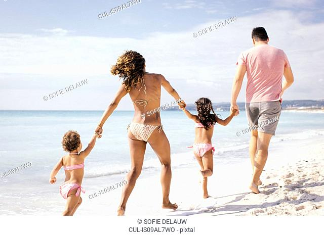 Couple and two girls running and holding hands on beach, Tuscany, Italy