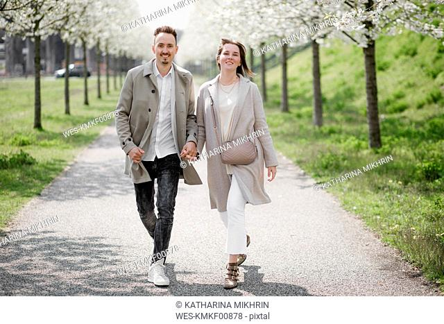 Affectionate couple strolling in a park in spring