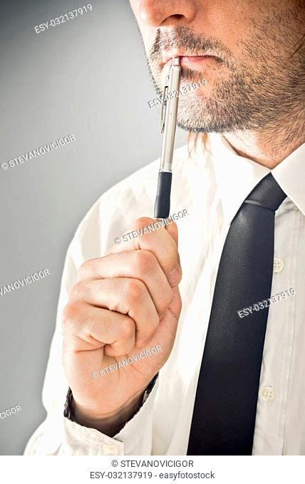 Businessman thinking with pencil in his mouth. Portrait of thoughtful business person