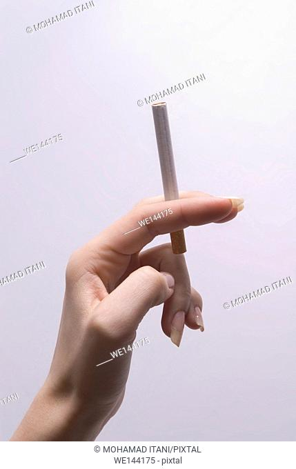 Woman's hand holding a cigarette against a white background