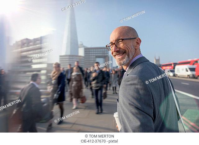 Portrait smiling businessman walking on busy urban sidewalk, London, UK