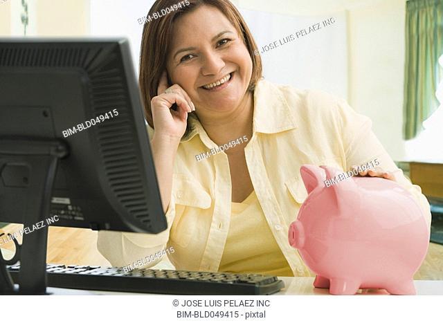 Hispanic woman with hand on piggy bank