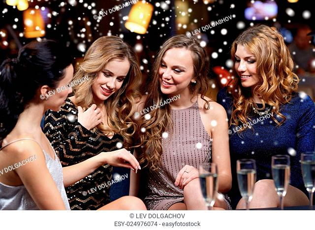 christmas, friends, bachelorette party and winter holidays concept - happy woman showing engagement ring to her friends with champagne glasses at night club...
