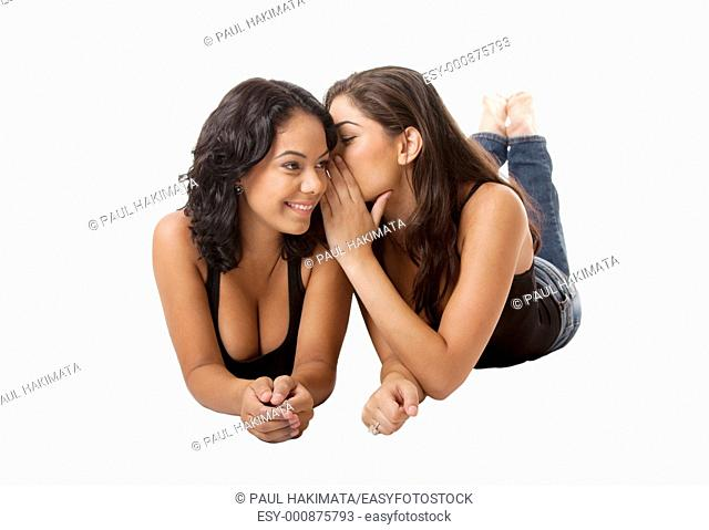 Two beautiful young happy women laying, sharing telling a gossip secret, isolated