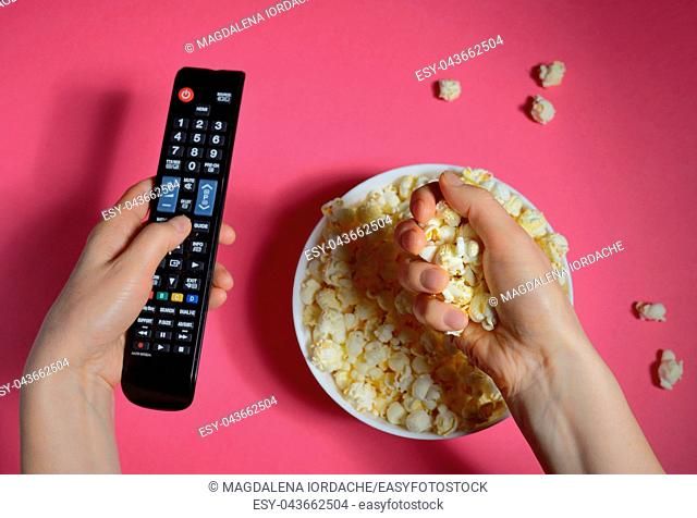Top view of hands holding remote controller and popcorn bucket isolated