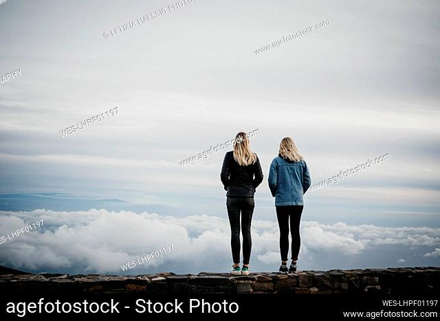 Rear view of female friends looking at idyllic cloudscape while standing at Haleakala Volcano, Hawaii, Maui, USA