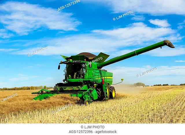 A farmer driving a combine with a full load ready to transfer with the auger arm extended during a Canola harvest; Legal, Alberta, Canada