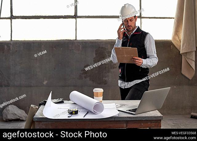 Male architect discussing over smart phone while analyzing document in building