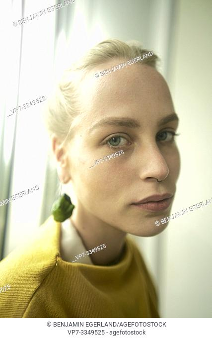 young sad woman wearing earring made of raw zucchini