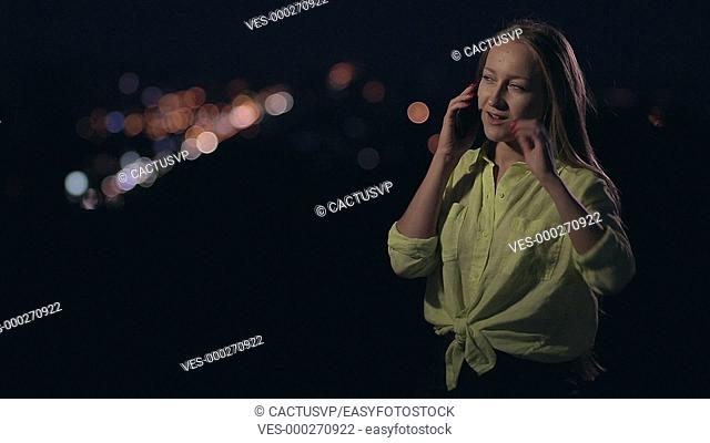 Happy woman talking on mobile phone at night