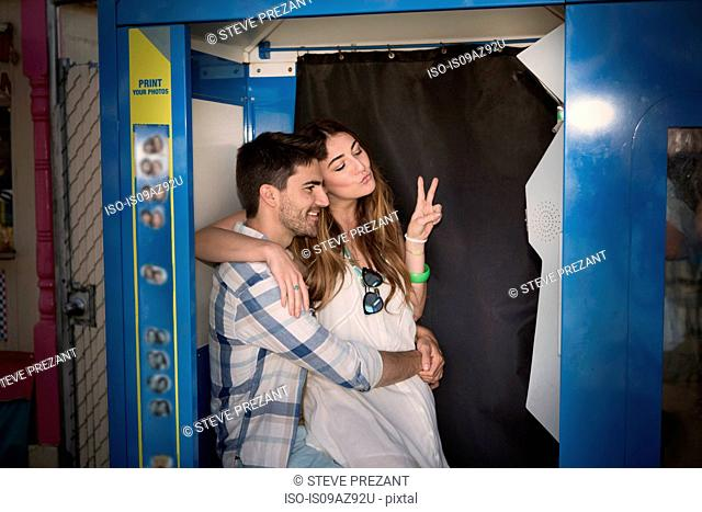 Couple in photo booth doing peace sign, Coney island, Brooklyn, New York, USA