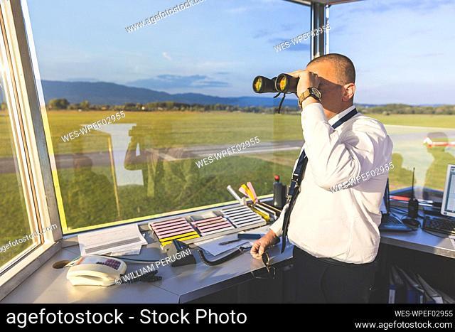 Pilot standing in control tower, using binoculars
