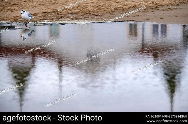 17 September 2021, Mecklenburg-Western Pomerania, Ahlbeck: The historic pier of Ahlbeck on the Baltic Sea island of Usedom is reflected in a body of water on...