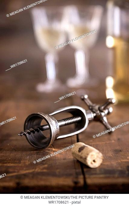 Large antique corkscrew laying on rustic wood surface. Wine bottle and glasses in background