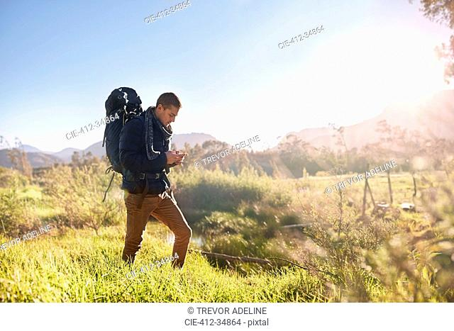 Young man with backpack hiking, checking compass in sunny, remote field