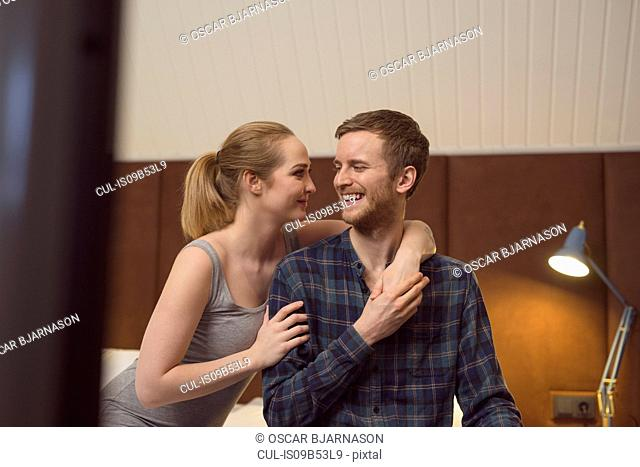 Young couple sitting on bed, face to face, smiling