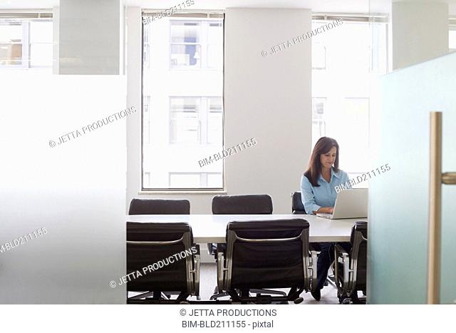 Caucasian businesswoman working in meeting room