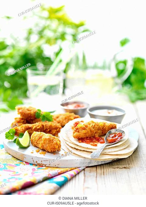 Mini crispy chicken fajitas with tortilla wraps, lime slice, tomato relish on garden table