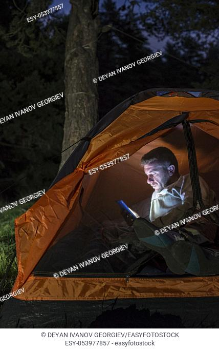 Man watching his smartphone in a tent at night