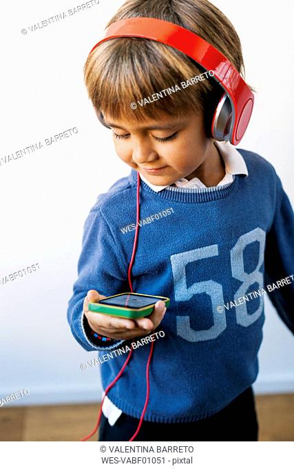 Little boy listening to music with headphones looking at smartphone