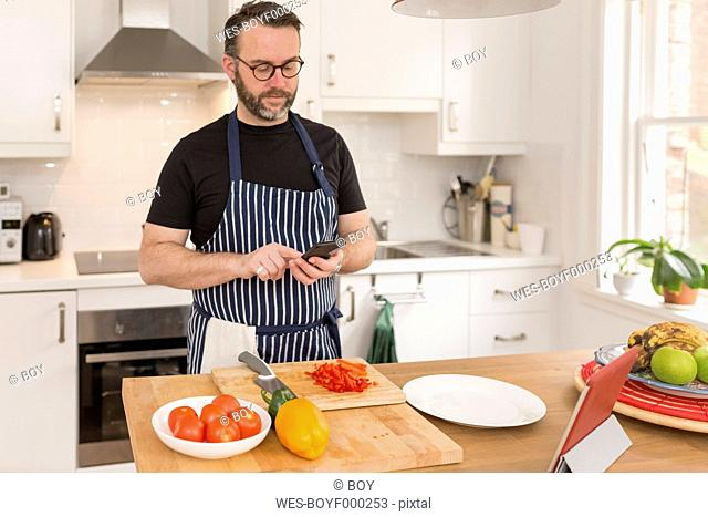 Portrait of man using smartphone while preparing food in the kitchen