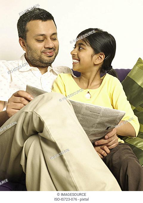 Father and daughter reading a newspaper