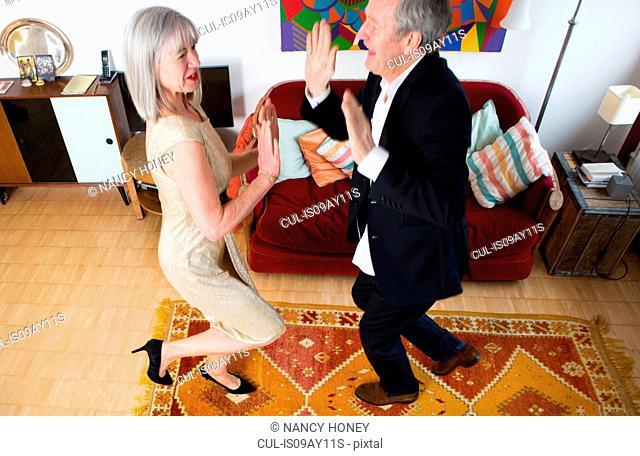 Couple dressed up and dancing at home