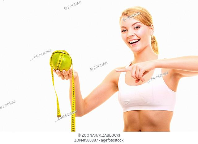 Happy woman holds grapefruit and measurement tape