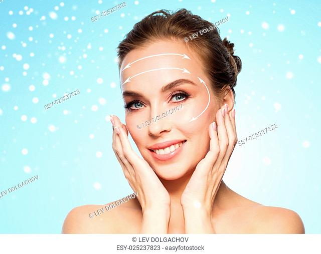 beauty, plastic surgery, facelift, people and rejuvenation concept - beautiful young woman touching her face with lifting arrows over blue background and snow