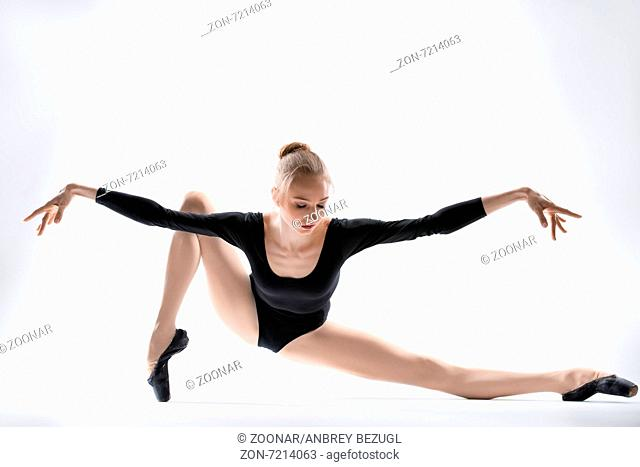 Graceful ballerina in black leotard doing stretching