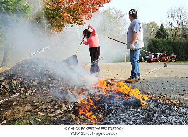 Couple raking and burning autumn leaves