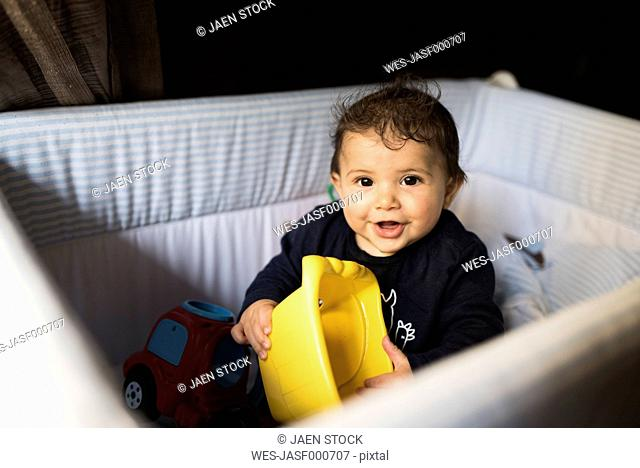 Portrait of smiling baby boy playing in cot
