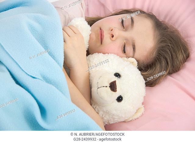 Little girl asleep in bed cuddling her teddy bear