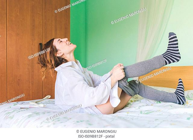 Laughing young woman on bed putting on leggings