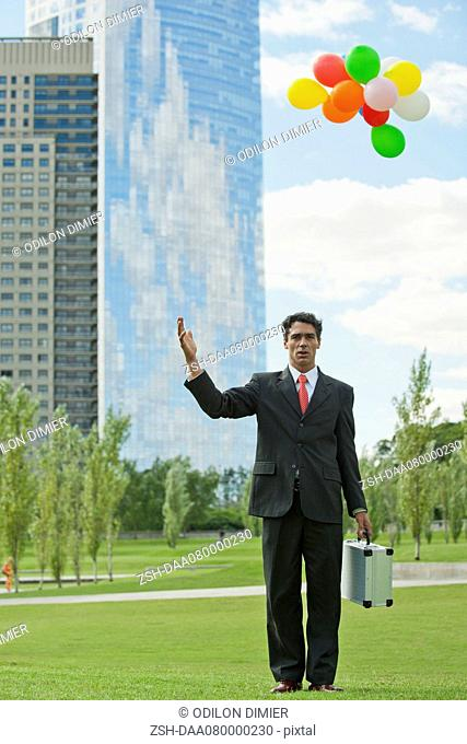 Businessman releasing bunch of balloons into air, looking disappointed