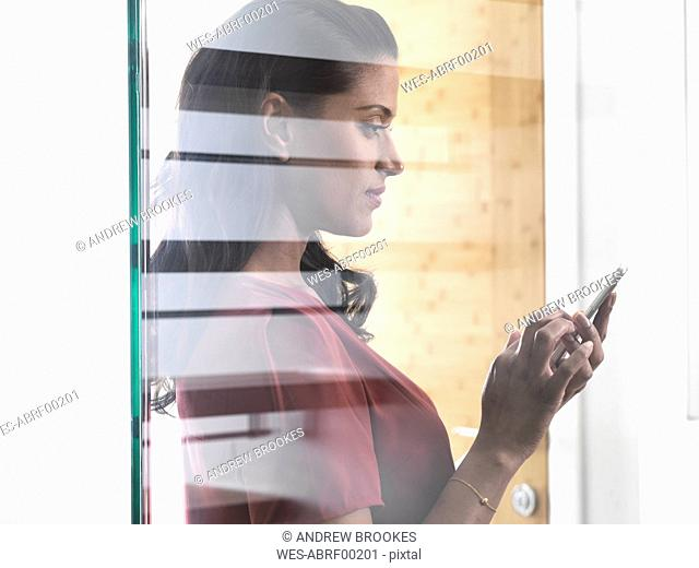 Profile of woman behind glass pane using smartphone