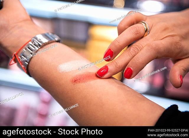 22 October 2020, Hamburg: A woman applies various eye shadows to her arm in a Douglas store on Jungfernstieg. Photo: Daniel Reinhardt/dpa