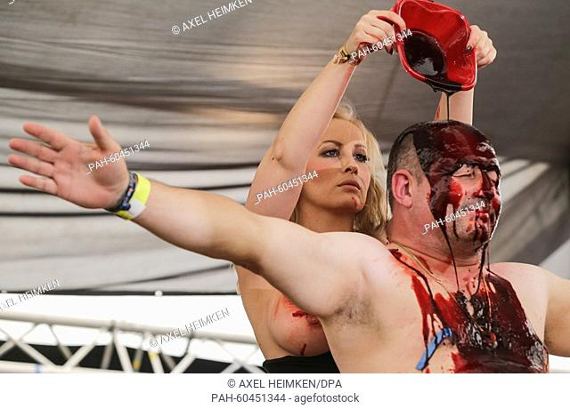 A member of the duo 'Blood Babes', who combine Striptease and artificial blood performs with a festival-goer at the Heavy Metal festival Wacken Open Air (W