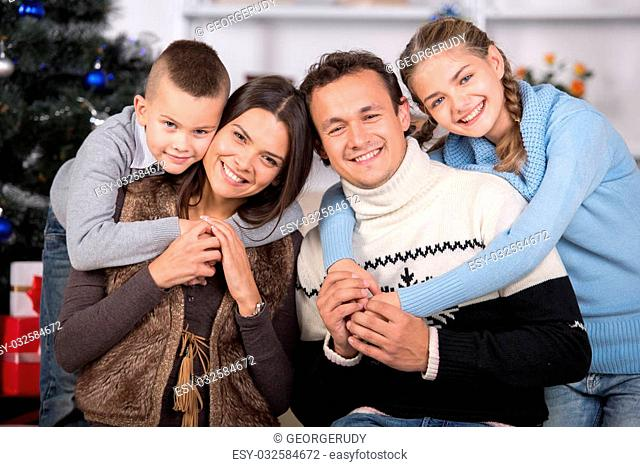 Portrait of friendly family are looking at camera on Christmas evening