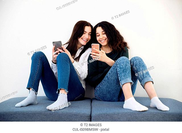 Two high school girls on seating looking at smartphones