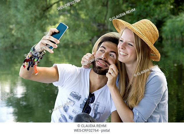 Playful young couple at a lake taking a selfie