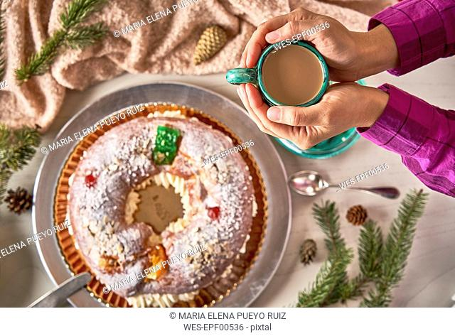 Hand holding cup of coffee above Spanish Christmas cake