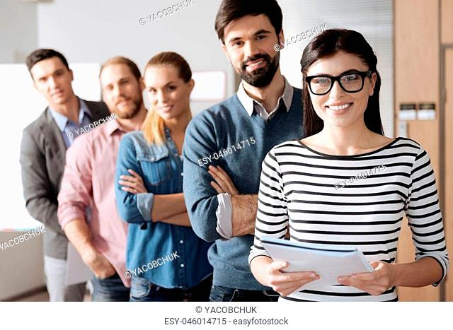 It is our team. Group of five coworkers standing in line crossing arms while posing on camera