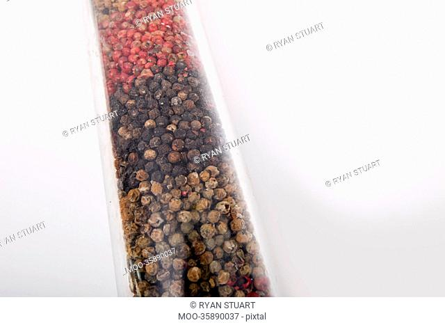 Various peppercorns in package against white background