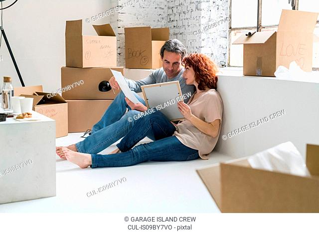 Couple moving into industrial style apartment, sitting on floor looking at pictures