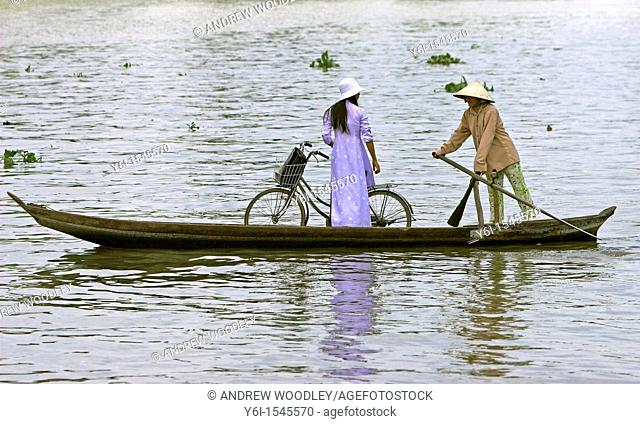 Woman in conical hat paddlling woman in ao dai with bicycle in ferry boat across Mekong Delta river Vietnam