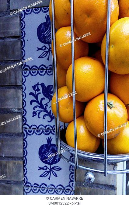 basket of oranges and squeeze machine